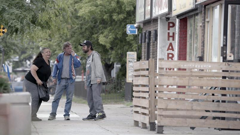 Three people stand outside o a Toronto street shrig a cigarette.