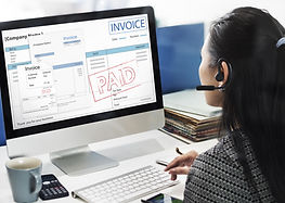 Lady on looing at invoices on he desktop screen