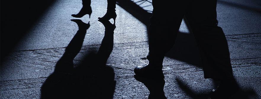 Suspicious man following woman in the dark