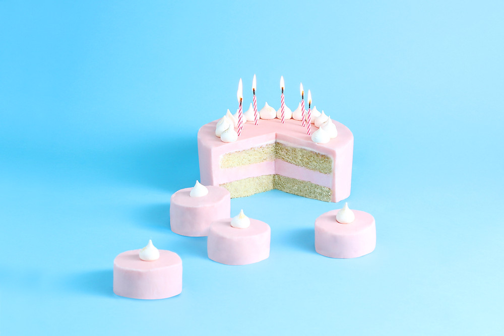 Pink birthday cake cut open with candles