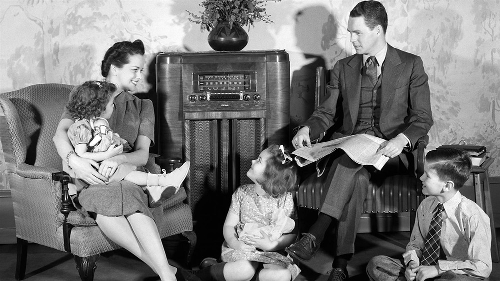 Black and white image of a family listening to a radio