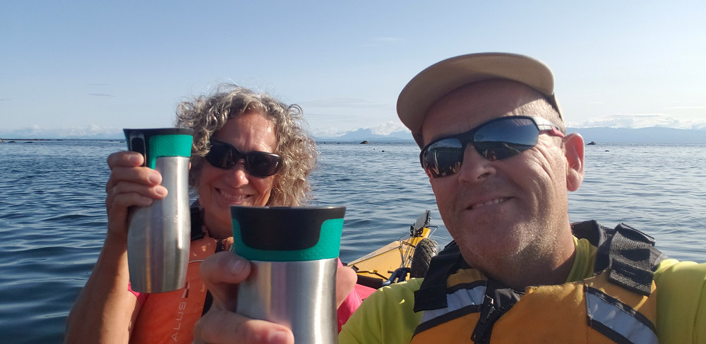 Rob Weiss and Jane Weiss drinking coffee while kayaking