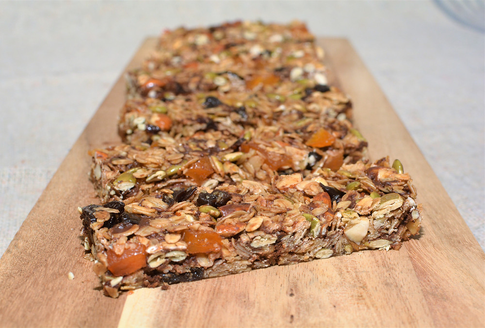 Cherry Apricot Nut and Seed Granola Bars with Dark Chocolate on wood board