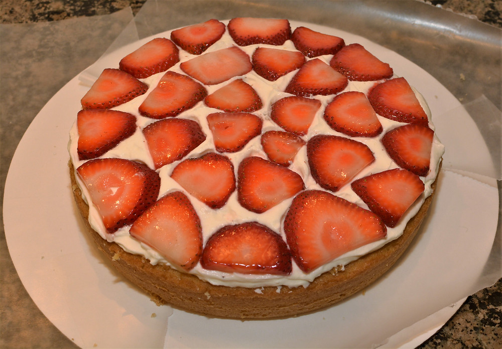 Vanilla Sponge Cake Layered with Whipped Cream Cheese Frosting and Strawberries