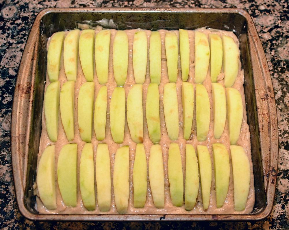 Apple slices arranged in Apple Cider Cake batter