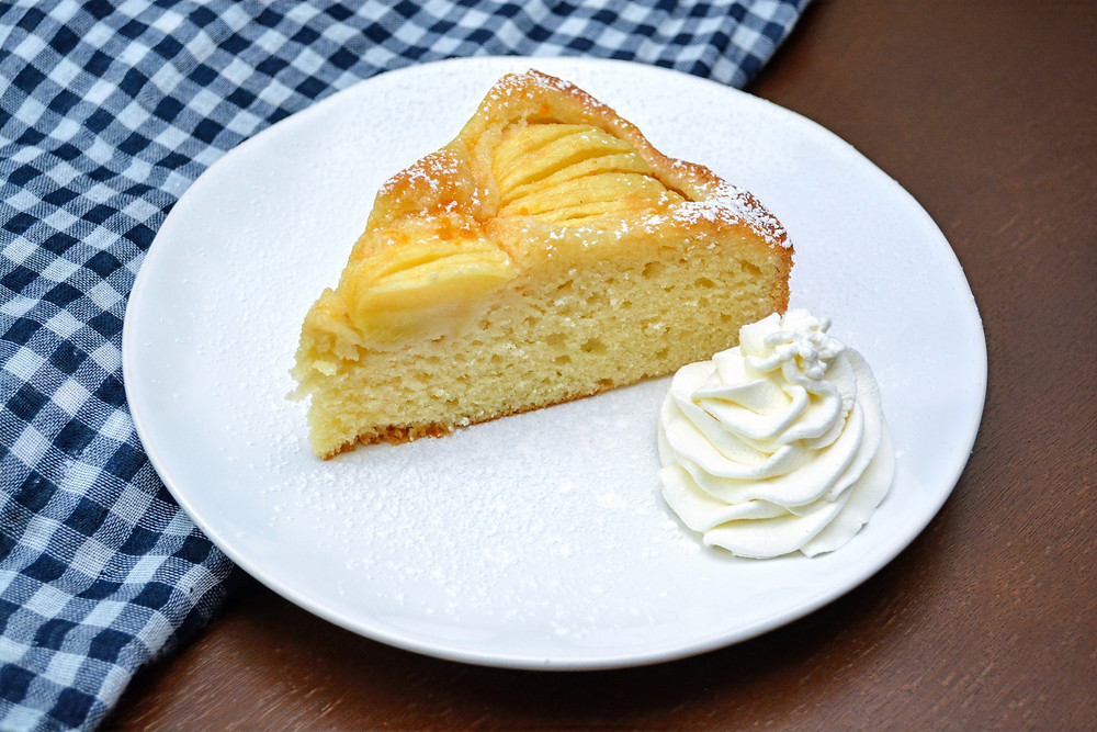 German Apple Cake with Confectioners' Sugar and Sweetened Whipped Cream