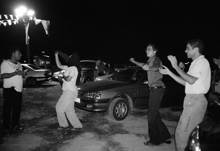 A man dons a headscarf and dances like a woman at a rest stop outside Tehran.