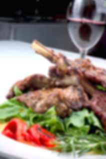 Tender lamb cutlets sautéed with garlic, vinegar and rosemary in a white wine sauce served on a bed of leaves.