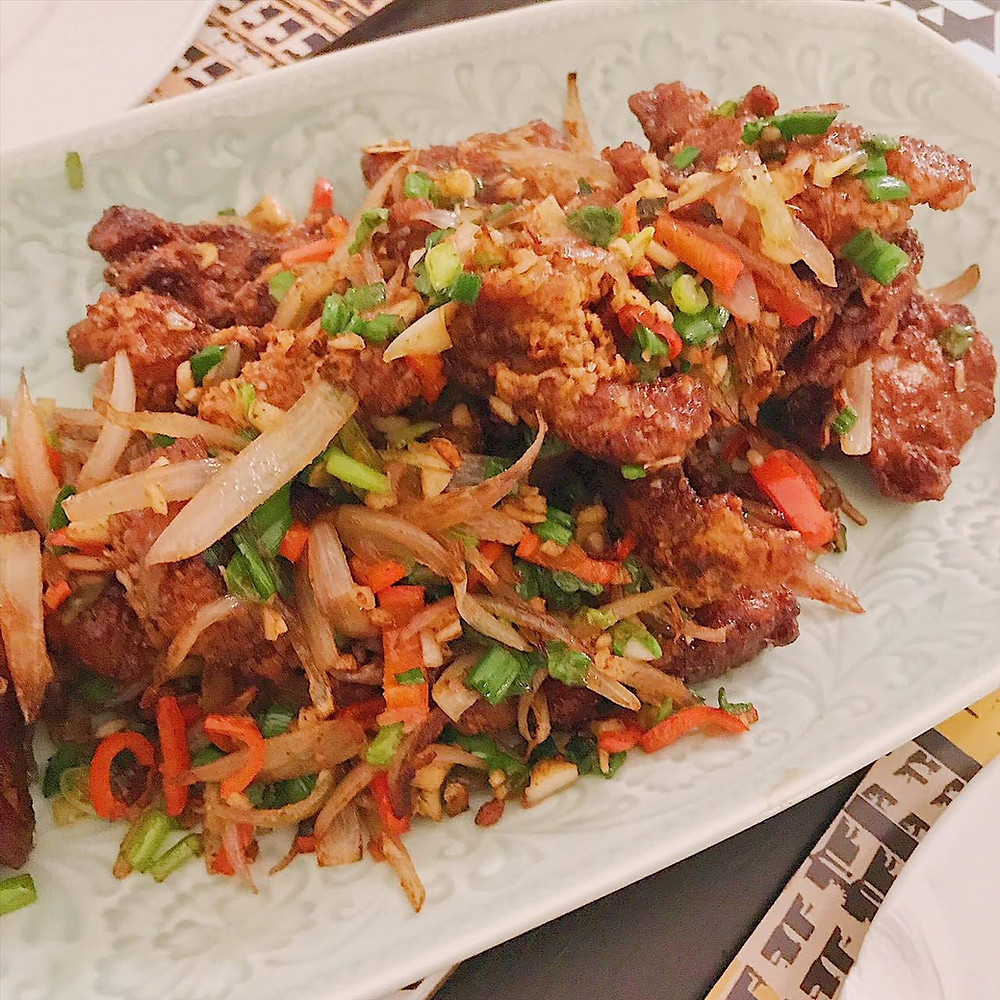 Deep fried pork cooked with chilli salt and pepper, red chillies, spring onions, onions and garlic