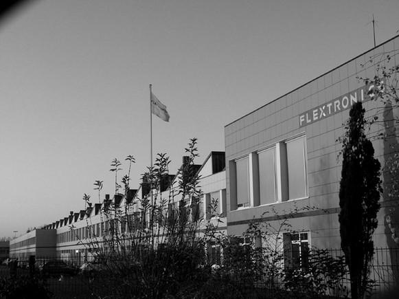"""Le 26 avril 2001, Alcatel vend son usine de Laval à Flextronics, un sous-traitant électronique américain basé à Singapour.  La totalité de sa production de téléphones cellulaires est confier à un groupe américain spécialisée dans la sous-traitance de produits électroniques.Le site de Laval compte 830 salariés lors de la cession de l'usine au sous-traitant Flextronics.  En octobre 2005, la direction de Flextronics annonce la fermeture du site de Laval, entrainant la suppression de 503 salariés.La direction de Flextronics déclare que la perte de son principal client, la co-entreprise franco-chinoise TCL Alcatel Mobile Phones, spécialisée dans les terminaux téléphoniques, ne permet d'assurer la pérennité du site industriel de Laval.  Photo """"Souvenirs de Mer"""" de Thierry Bressol Usine Flextronics Laval"""