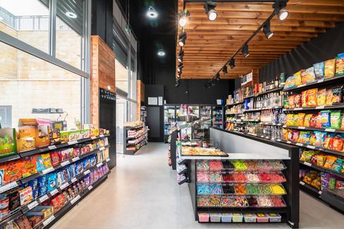 מבט על כל החנות מצד שמאל וימין מדפים עם חטיפים ובאמצע תאים שקופים עם סוכריות גומי