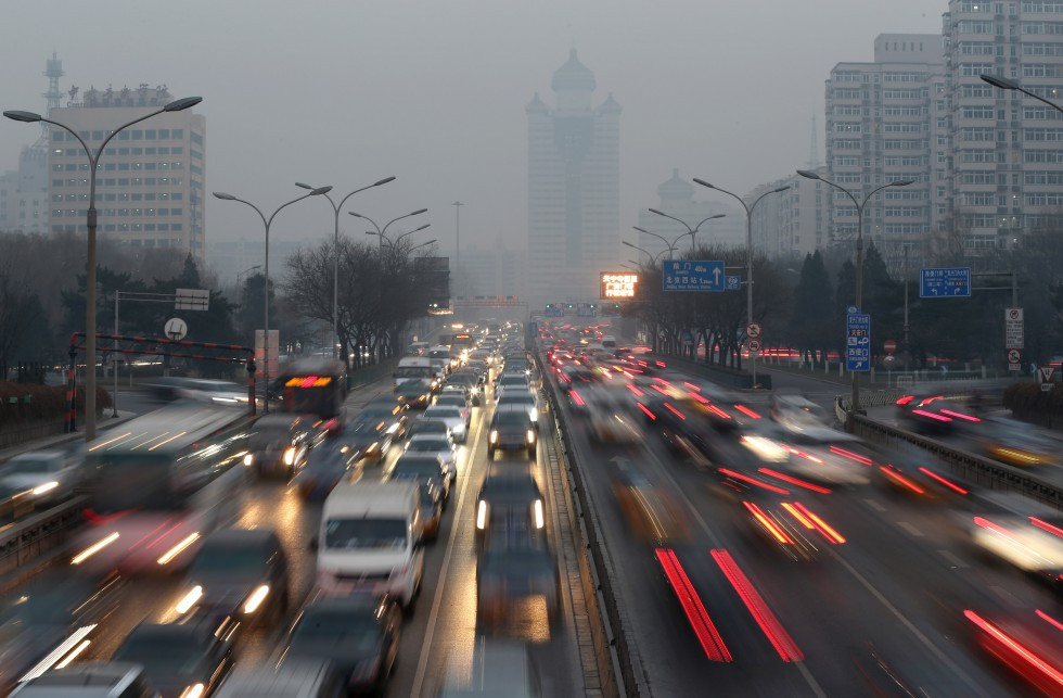(Traffic runs amid heavy smog in Beijing on December 29. The government hopes to improve environmental conditions by promoting a shift to clean energy vehicles. Photo: Xinhua