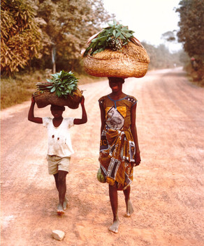 Julia Mah and her brother returning to the village from the family farm at the end of a work day, rice and greens for that night's meal balanced on their heads.