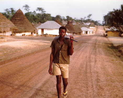 Josiah Peye, my friend and contemporary, walking down Kpaytuo's main—and only—road, on his way to hunt game.