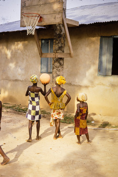 Three young girls learning to play basketball on a backboard made of mahogany, a tree found in Liberia's rain forest.