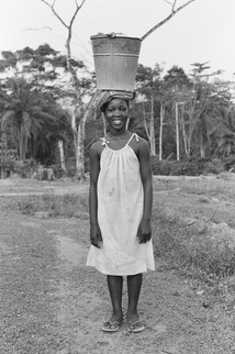 A young girl returning from the well, the first of many 30-minute round-trips she and her counterparts, who included young boys, made daily.