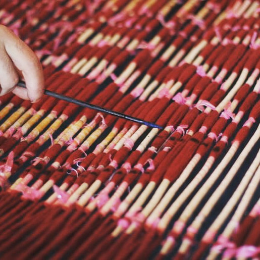 The artisan responsible for transforming the paper pattern into actual, woven cloth again marks the livits to show the binders which sections need to be untied and which sections tied for the next dye bath, which will be blue.