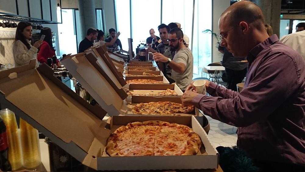 *写真はオフィスで行われたピザパーティー、ピザはコシェルのビザ。