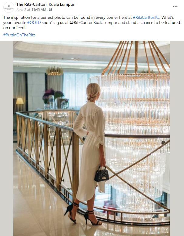 Woman looking at chandelier at Ritz Carlton KL.