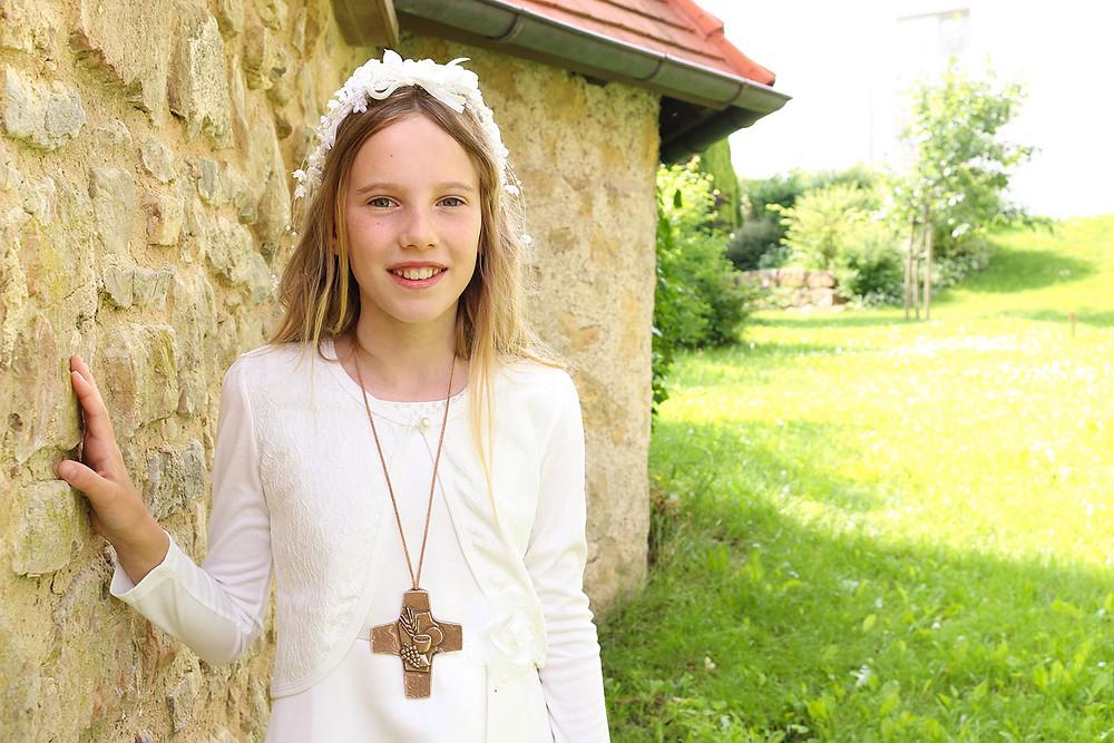 Kommunkionskind Finja steht im Grünen und lehnt an der Kirchenmauer der Pfarrkirche St. Mauritius in Horb-Nordstetten.