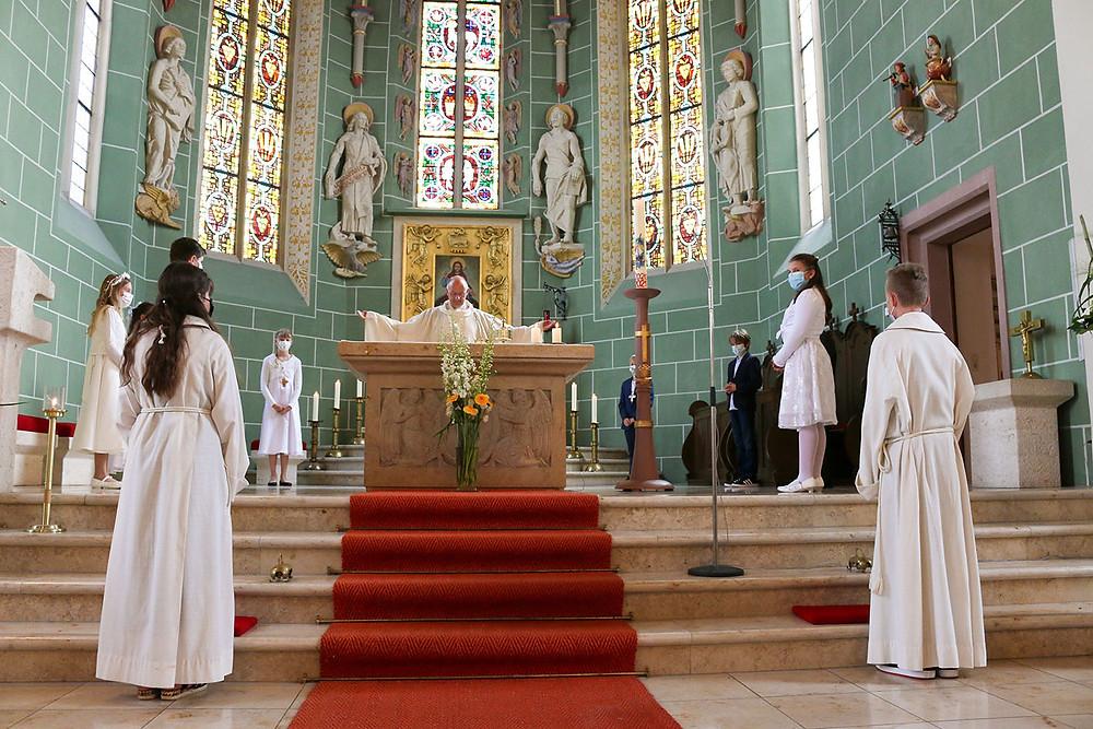Der Priester steht am Altar und segnet die Kommunionskinder.