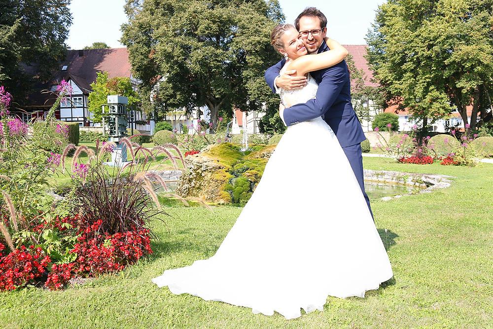 Hochzeitsshooting im Park von Schloss Dätzingen. Das Brautpaar umarmt sich vor dem Brunnen.