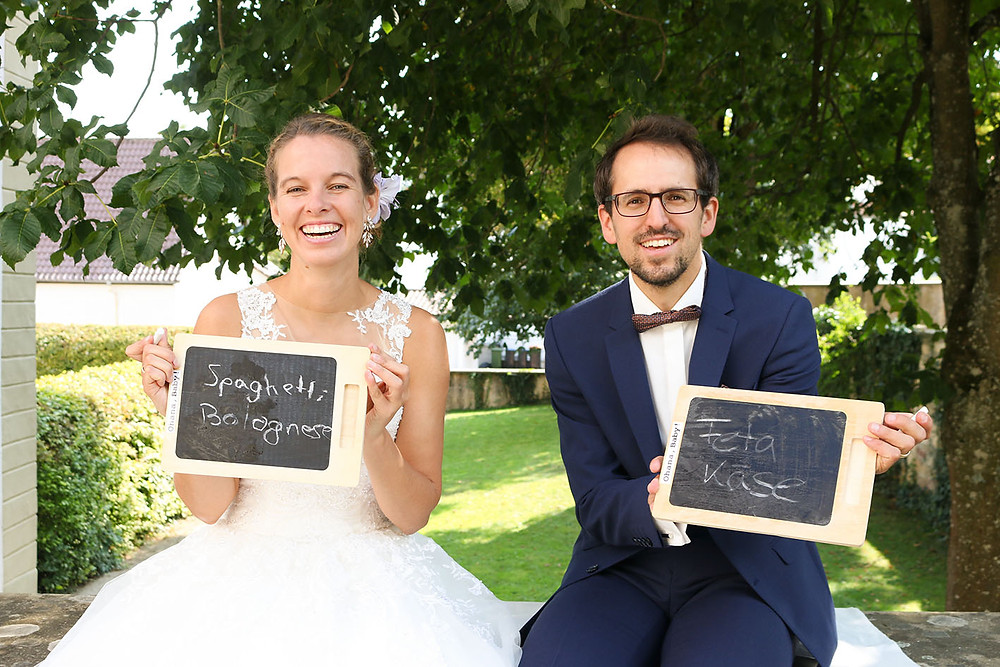 Das Brautpaar hält die Tafeln in die Kamera. Das Lieblingsessen des Bräutigams ist Spaghetti Bolognese. Die Braut liebt dagegen Fetakäse.