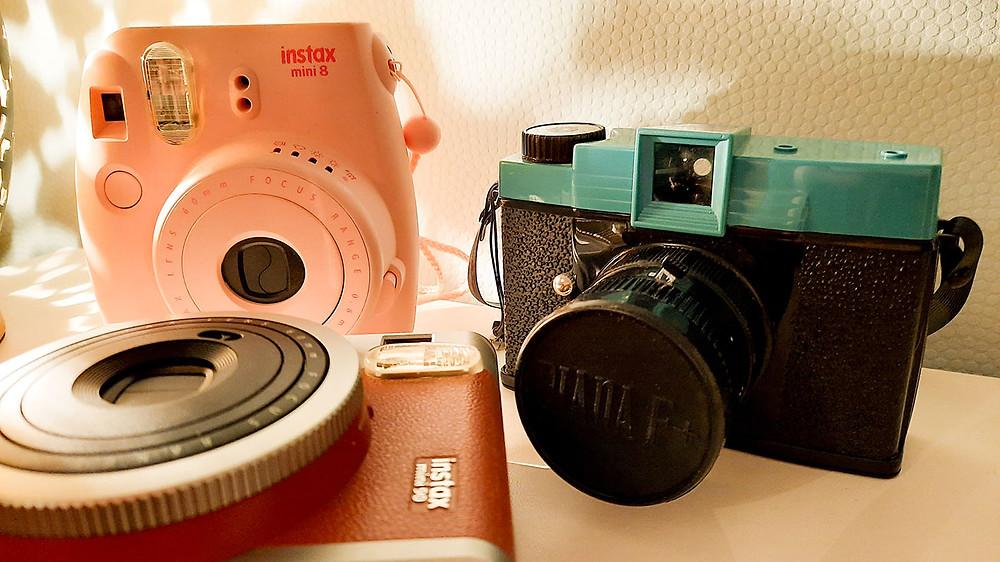 Drei Sofortbildkameras: Instax mini 8 in rosa, Instax in brauner Retrooptik und die Lomographie-Kamera Diana F.