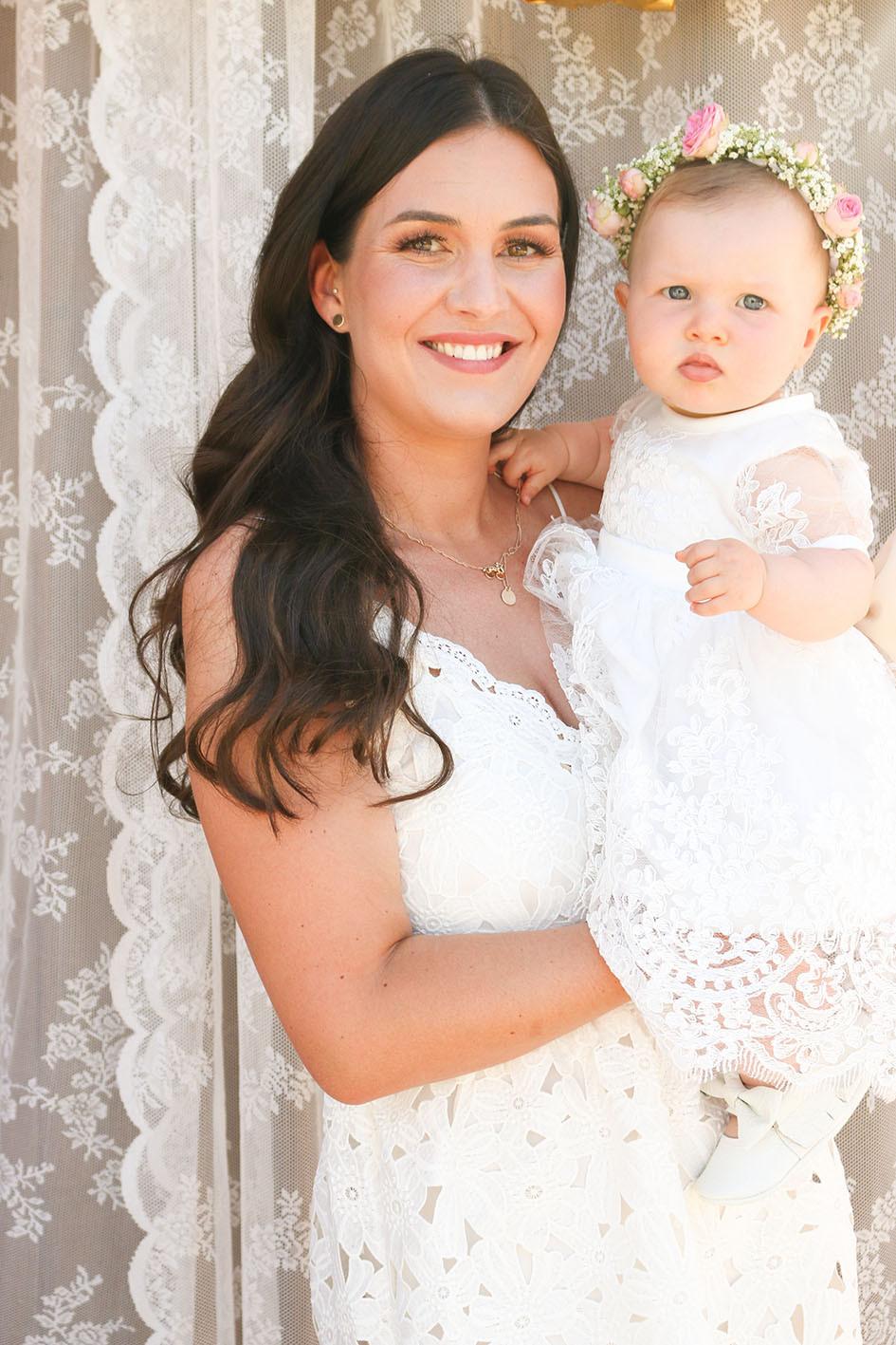 Mama Tabea hält Baby Mila auf dem Arm. Beide tragen ein weißes Kleid.