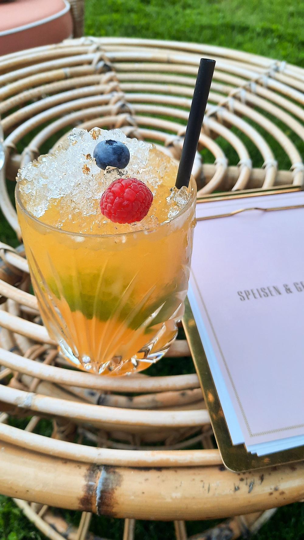 Cocktail Fernblick-Caipi mit Obst-Deko und Goldstaub.