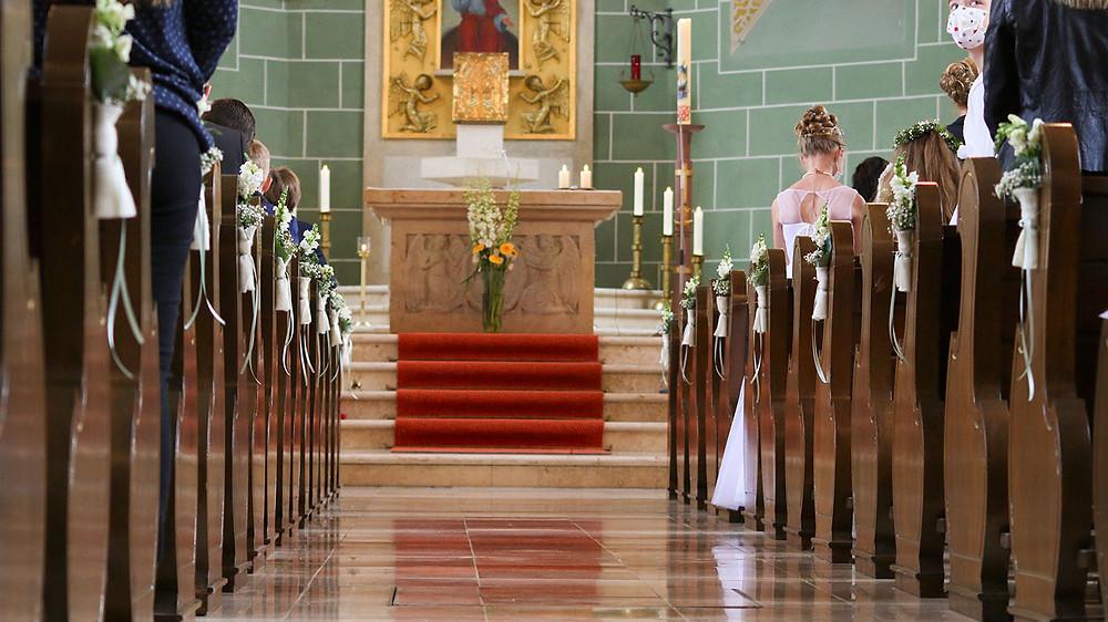 Die Gemeinde erhabt sich von den Bänken. Im Fokus der Altar.