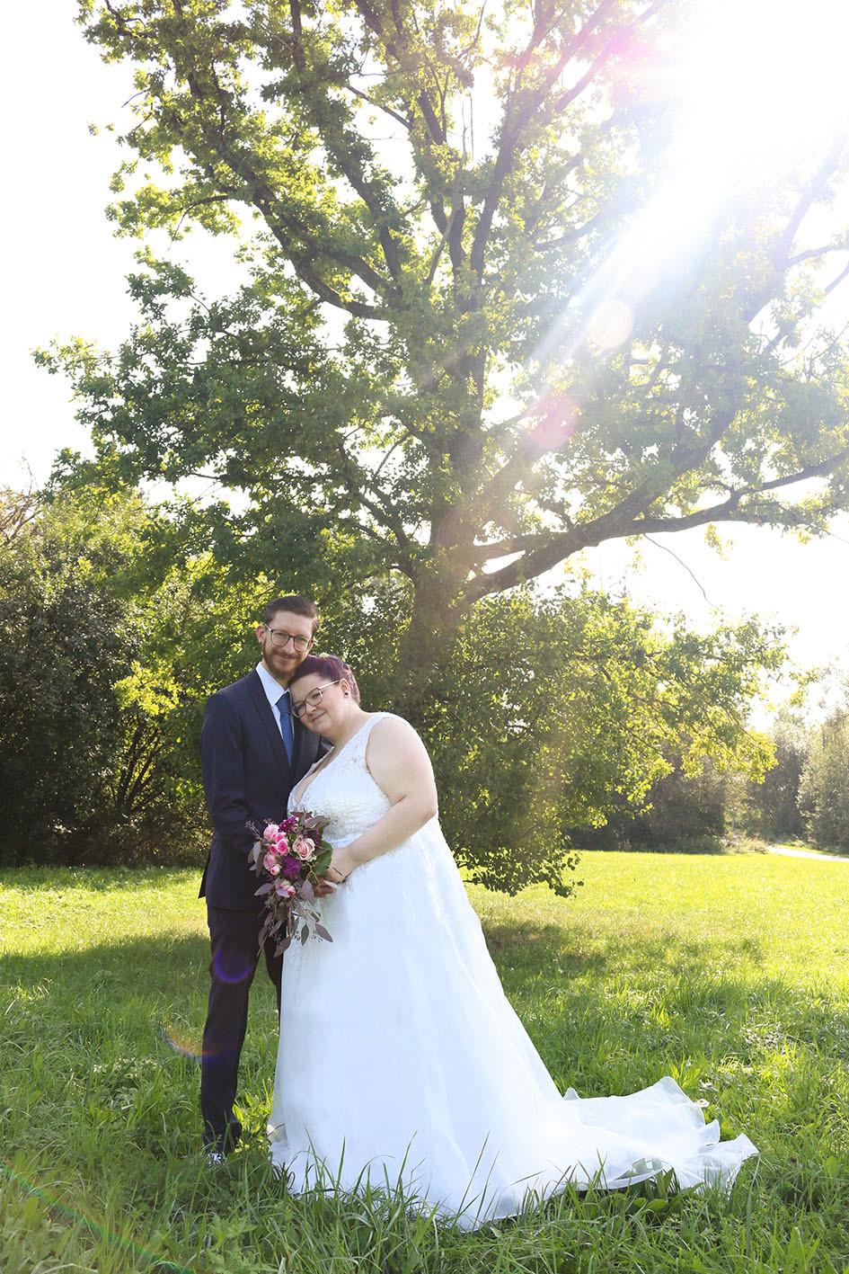 Christian hält seine Nina im Arm. Im Hintergrund steht ein riesiger Baum durch den die Sonne auf das Brautpaar strahlt.