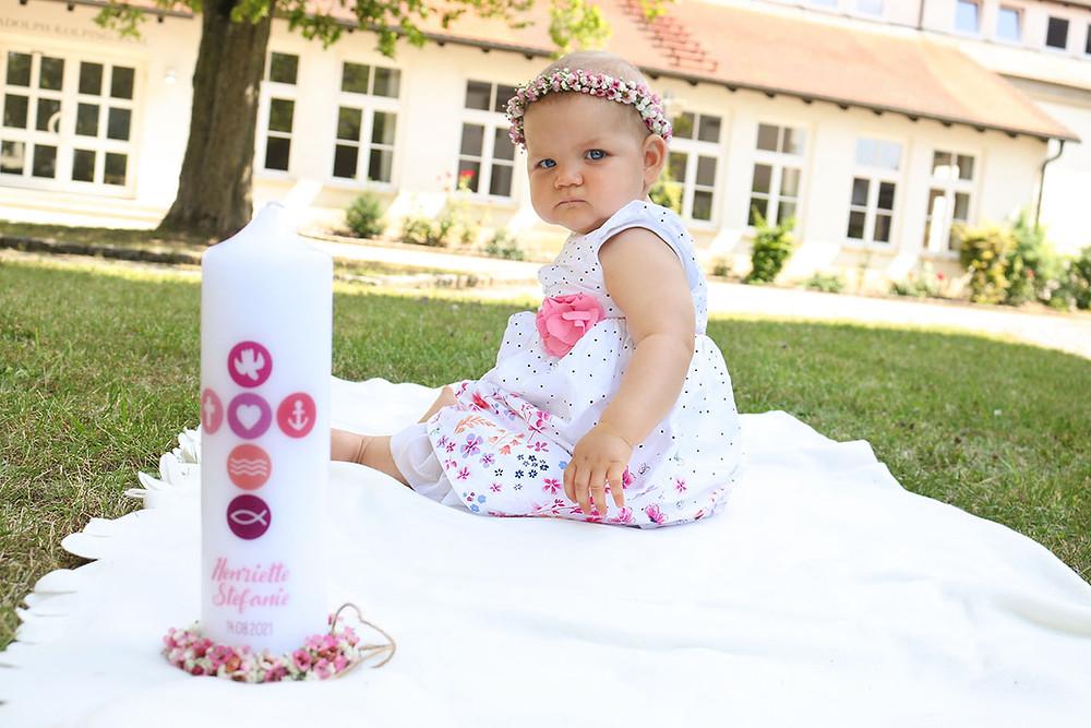 Baby Henriette sitzt auf einer weißen Decke. Im Vordergrund steht ihre Taufkerze.