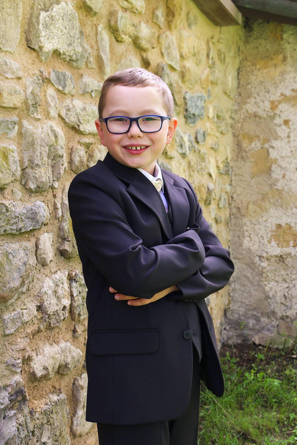 Kommunionskind mit Brille posiert vor der Kirchenmauer.