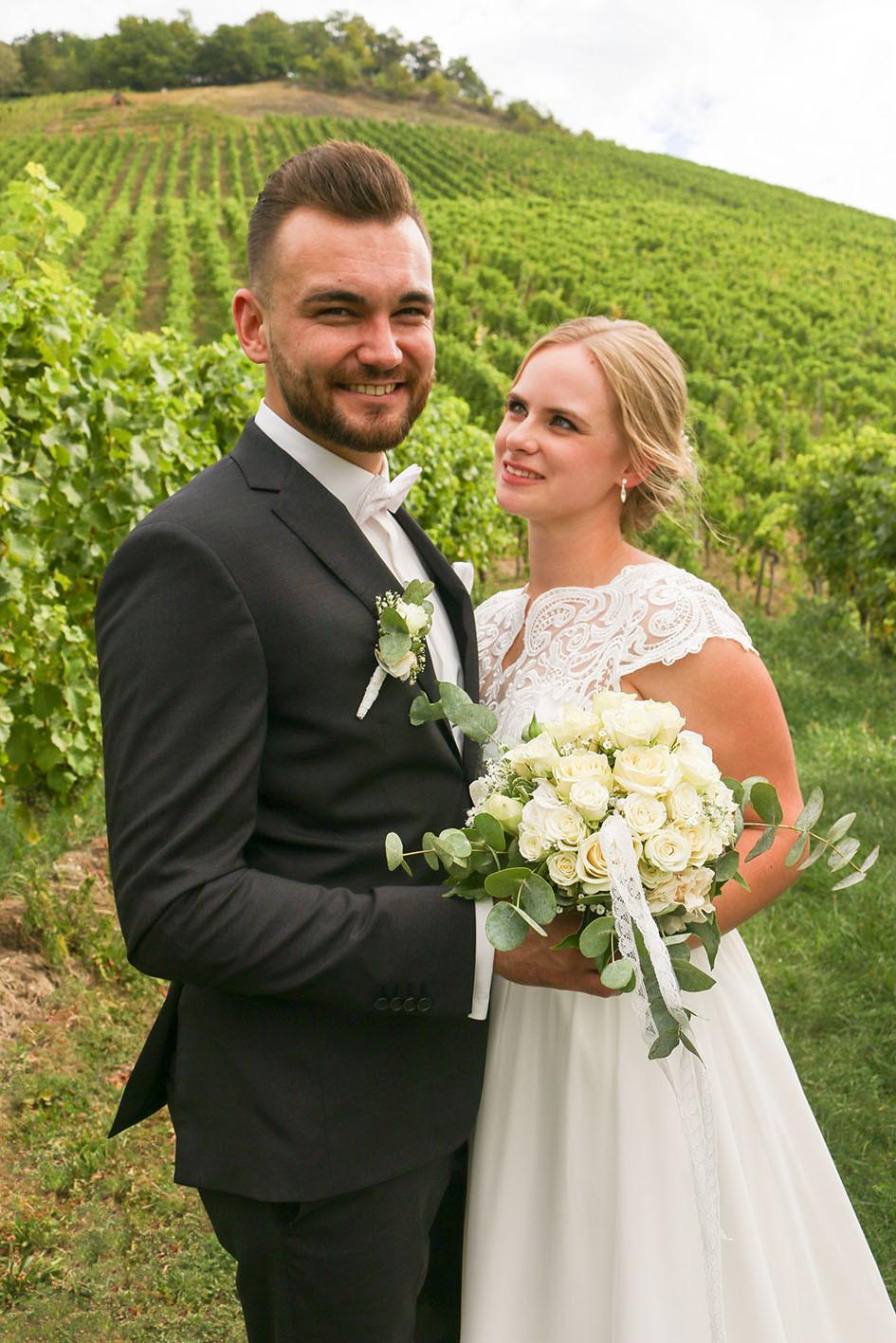 Braut Yvonne lächelt ihren Dennis an. Im Hintergrund sind die Weinberge von Korb zu sehen.