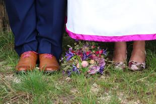 Detailfoto: Brautschuhe und Bräutigamschuhe mit Brautstrauß.