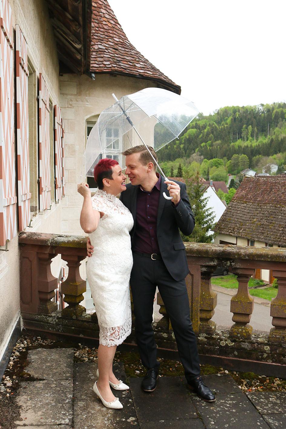 Braut und Bräutigam mit Regenschirm auf dem Balkon von Schloss Glatt.