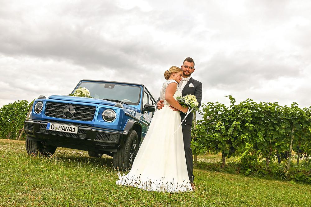 Das Brautpaar mit dem Hochzeitsauto: einer brillantblauen Mercedes G-Klasse.