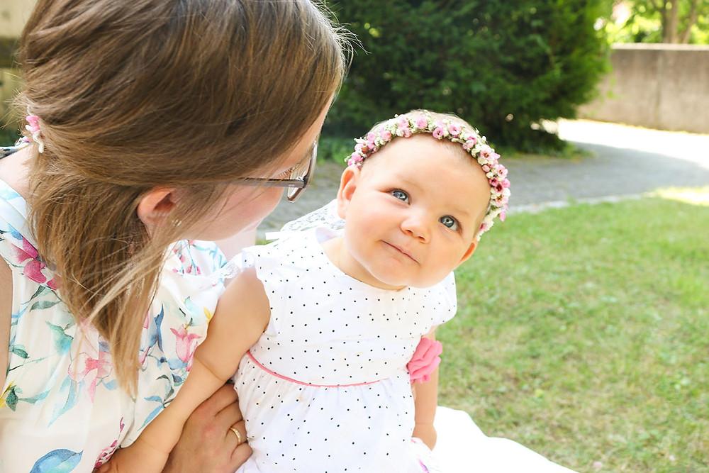 Baby Henriette sitzt auf dem Schoß ihrer Mutter.