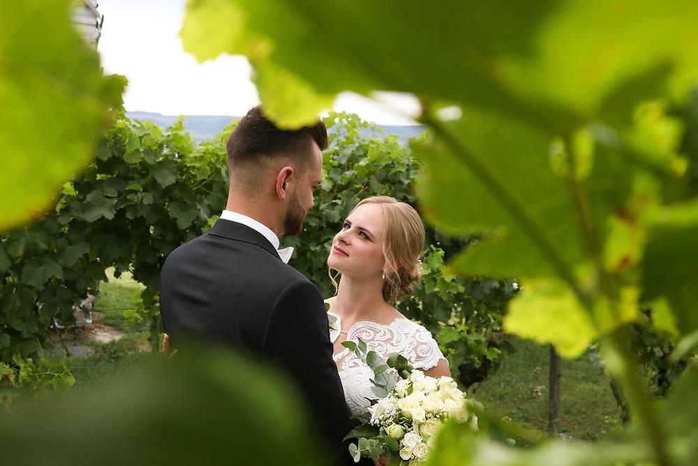 Sicht durch die Weinreben. Dennis hält Yvonne im Arm. Sie blickt ihm tief in die Augen.
