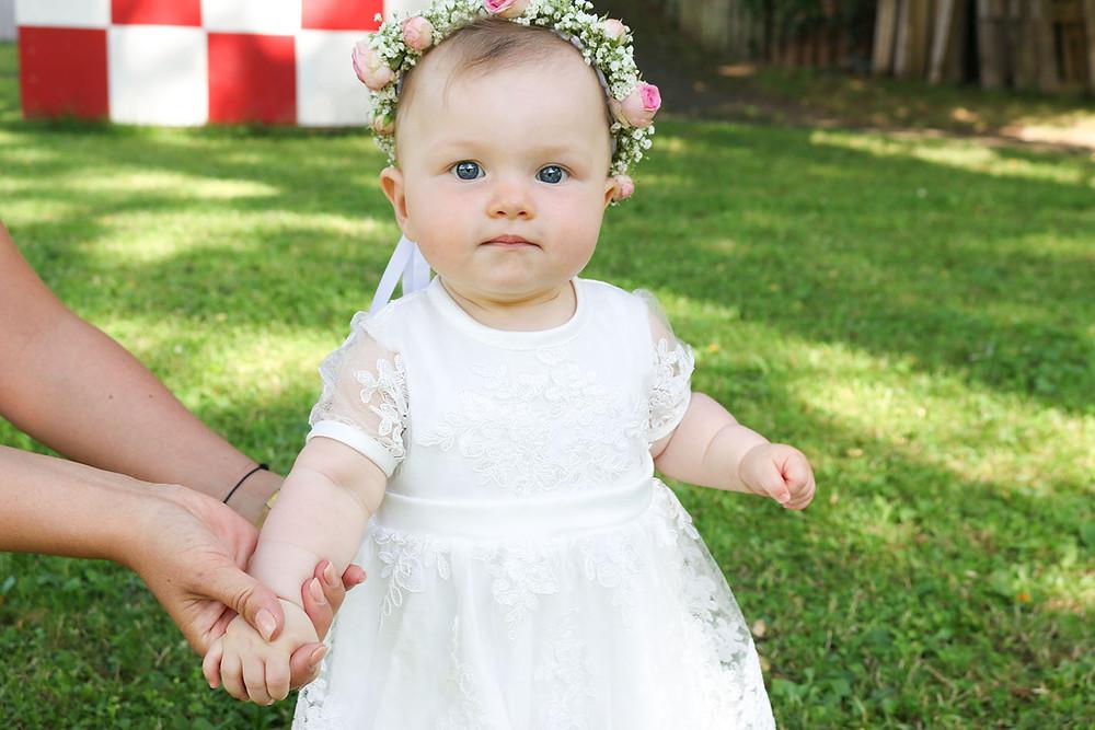 Baby Mila in ihrem hünschen weißen Taufkleid.