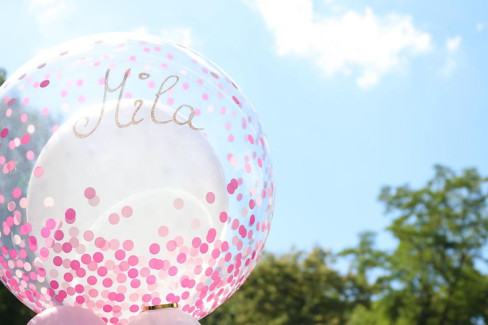 Ein Ballon mit rosa Konfetti und dem Namen Mila. Im Hintergrund der blaue Himmel und Bäume.