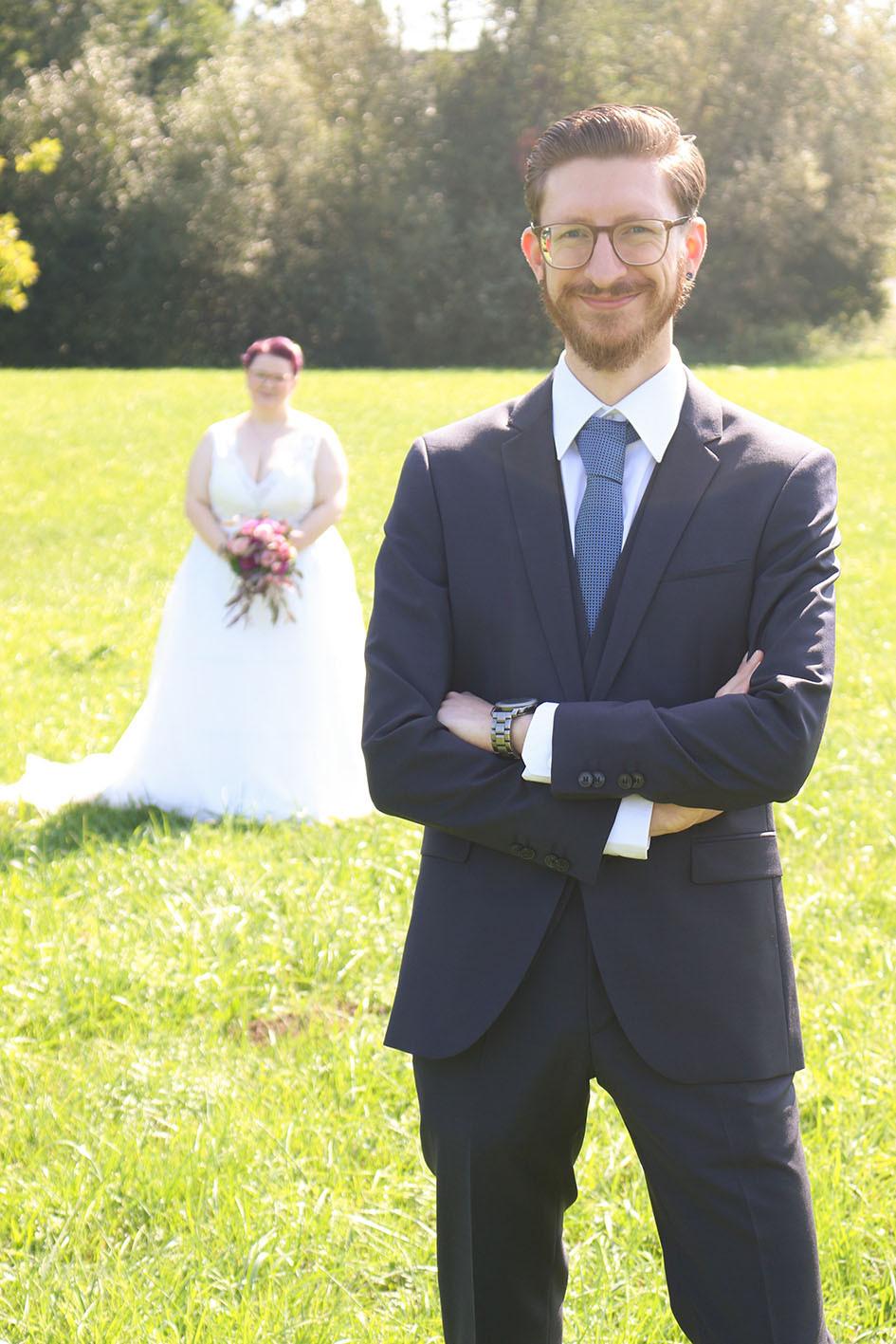 Christian steht im Vordergrund, Nina im Hintergrund. Beide tragen ihre Hochzeitskleidung.