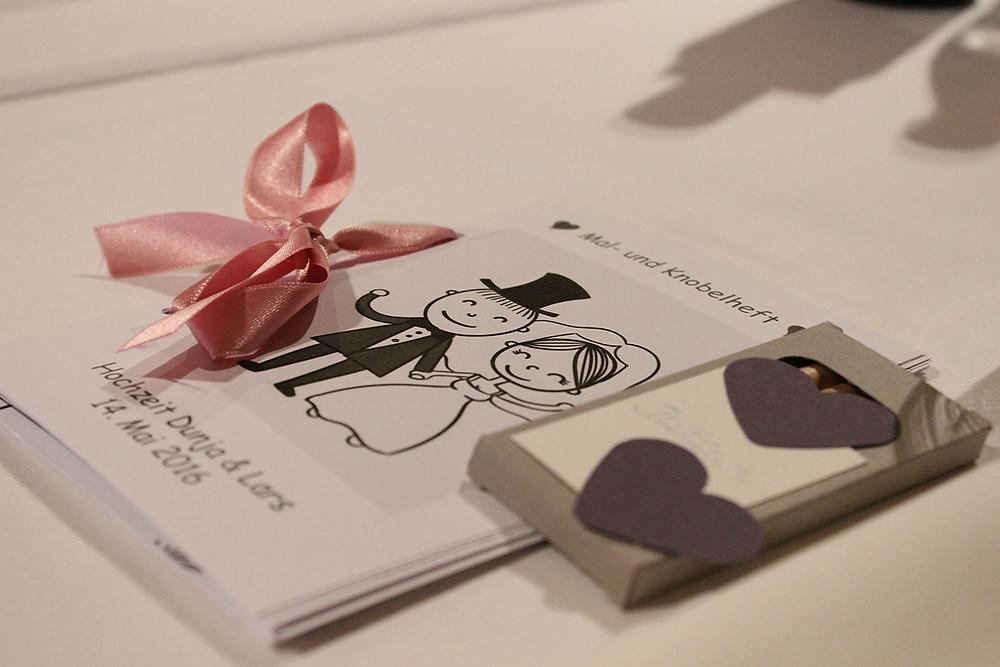 Ein kleines Malbuch mit Schleife und Stiften liegen auf dem Tisch.