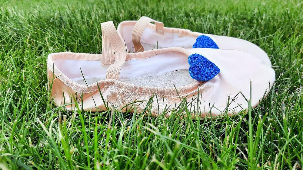Rosafarbene Ballettschläppchen mit blauen Herzen liegen im Gras.