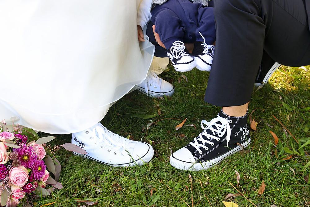 Die Schuhe im Fokus: Braut, Bräutigam und der kleine Säugling tragen Schuhe im Converse-Stil.