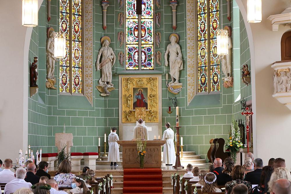 Kirchenzeremonie in der Pfarrkirche St. Mauritius in Horb-Nordstetten. Am Altar steht der Priester und die Ministranten.