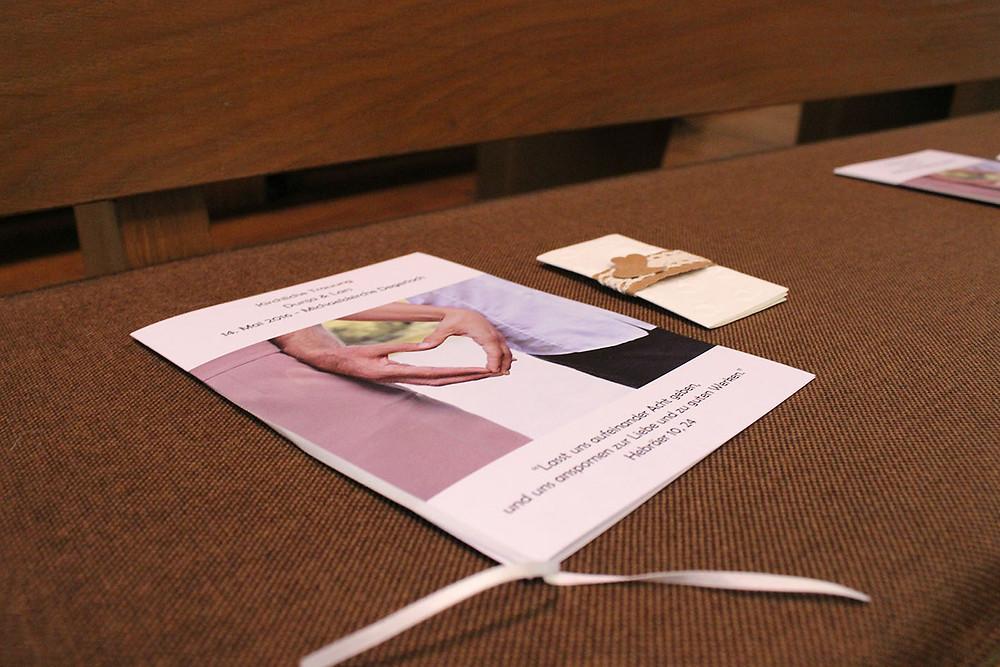 Gesangsauszug und Taschentuch liegen auf der Kirchenbank.