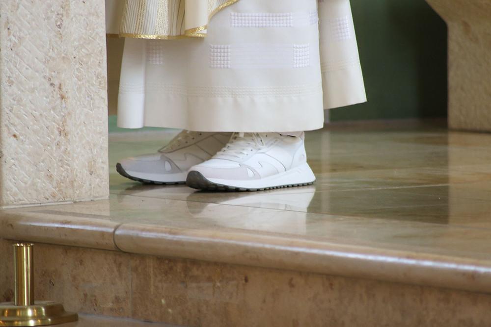 Der Priester trägt weiße moderne Sneaker.