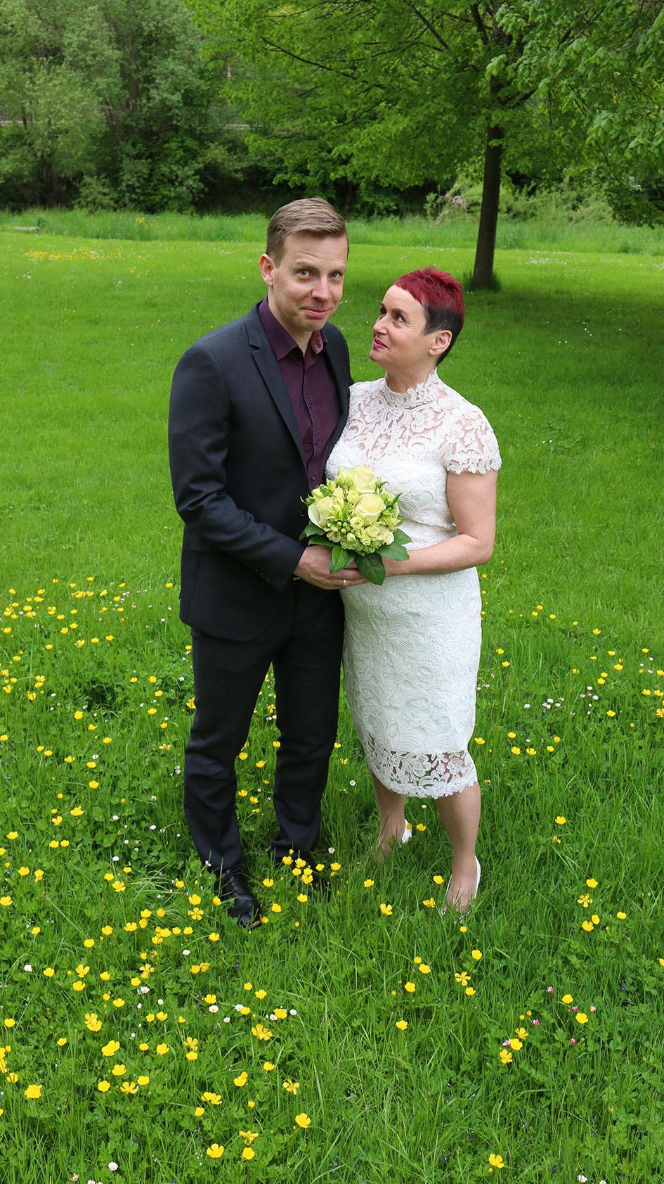 Das Brautpaar steht auf einer Grünfläche im Park.